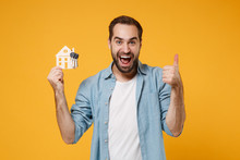 Excited Young Man In Casual Blue Shirt Posing Isolated On Yellow Orange Wall Background, Studio Portrait. People Lifestyle Concept. Mock Up Copy Space. Hold House And Bunch Of Keys, Showing Thumb Up.