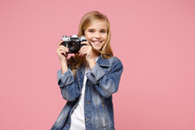 Smiling Little Blonde Kid Girl 12-13 Years Old In Denim Jacket Posing Isolated On Pastel Pink Background In Studio. Childhood Lifestyle Concept. Mock Up Copy Space. Hold Retro Vintage Photo Camera.