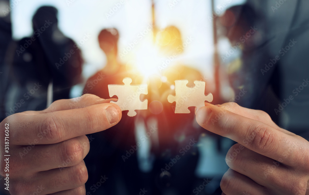 Fototapeta Businessman join two puzzle pieces. Concept of teamwork and partnership. double exposure with light effects
