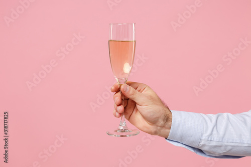 Fotomural Close up cropped photo of male hold in hand glass of champagne isolated on pastel pink wall background