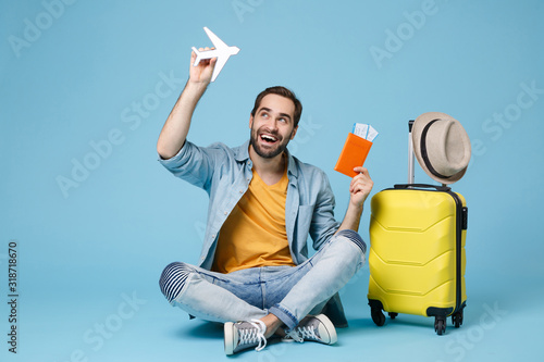 Fototapeta Funny traveler tourist man in yellow clothes isolated on blue background. Passenger traveling abroad on weekend. Air flight journey Sit near suitcase hold passport boarding pass tickets air plane. obraz