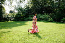 African American Woman In Summer Dress Backlit On A Lawn During Summer