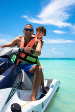 Father And Son Sitting On Jet Boat