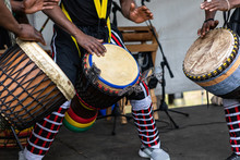 Closeup Of Three Artist Performing Traditional Colorful String Wrapped African Djembe Drums While Standing On Stage During Event