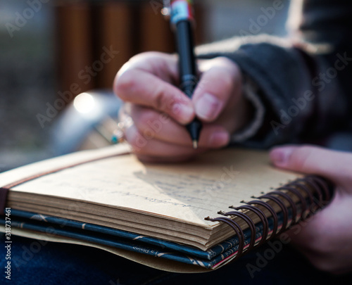 Close-Up Of Hand Writing In Diary Canvas Print