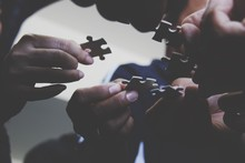 Close-Up Of Hands Holding Jigsaw Pieces