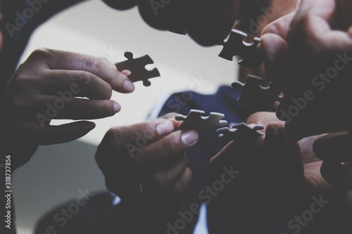 Close-Up Of Hands Holding Jigsaw Pieces - fototapety na wymiar
