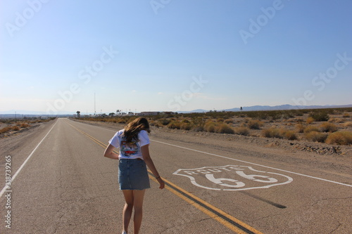 Wallpaper Mural Rear View Of Woman Standing On Route 66 Against Blue Sky