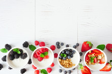 Healthy Yogurt Bowls With Assorted Berries And Granola. Bottom Border Against A White Wood Background. Copy Space.