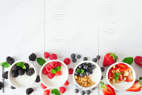 Fototapeta Healthy yogurt bowls with assorted berries and granola. Bottom border against a white wood background. Copy space. obraz