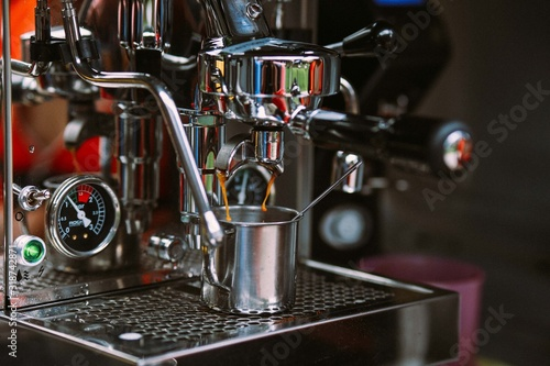 Fotografering Coffee Pouring In Cup From Machinery