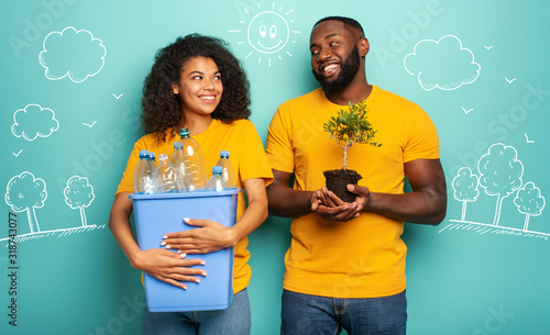 Cuadros en Lienzo Happy couple hold a plastic container with bottles and a small tree over a light blue color