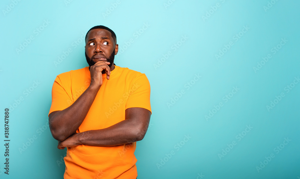 Fototapeta Confuse and pensive expression of a boy . cyan colored background