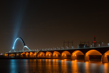 LOW ANGLE VIEW OF ILLUMINATED BRIDGE OVER RIVER AT NIGHT