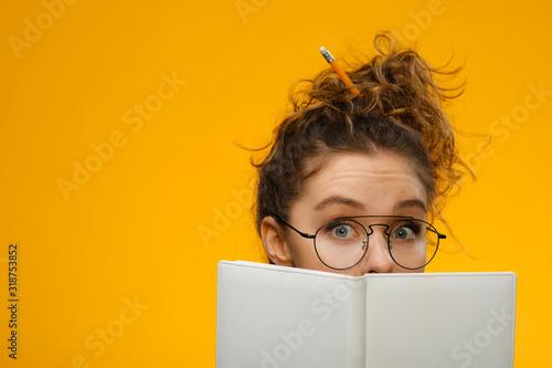 Cuadros en Lienzo Closeup portrait of teenager hiding behind notebook