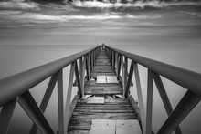 Mid Distance Of Person Standing On Broken Pier Over Sea