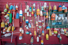 Fishing Buoys On Wall Of House