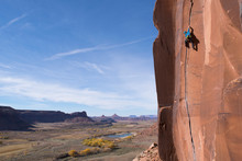 Low Angle View Of Man Rock Climbing Against Blue Sky