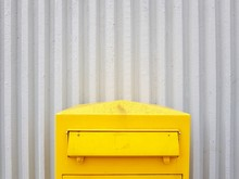 Yellow Mailbox Against Corrugated Iron