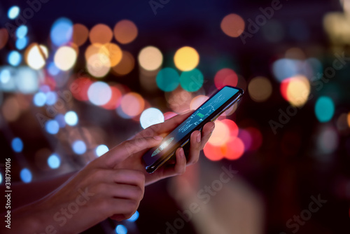 Fotografía Close-up of hands scanning fingerprint on smartphone to unlock mobile phone on bokeh colors light in night atmospheric city, Concept security in identity technology