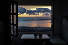 View Of Sea Seen Through Window During Sunset
