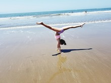 Full Length Of Girl Doing Handstand At Beach During Sunny Day