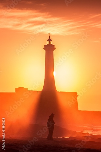 Silhouette Of Man Standing Against Lighthouse Against Sky During Sunset Fotobehang