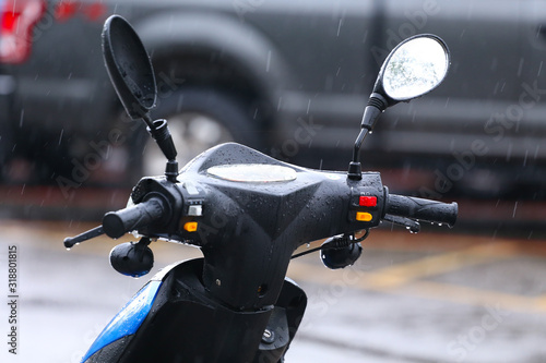 Fototapeta Close-Up Of Motor Scooter Parked On Road During Rain