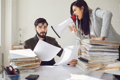Angry boss businesswoman shouting at her office worker in a megaphone in the office