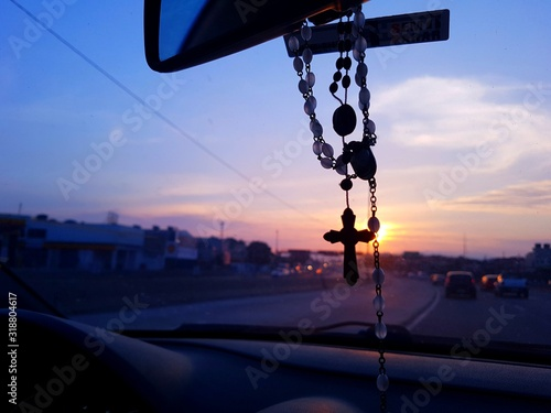 Rosary Hanging In Car During Sunset Fototapet