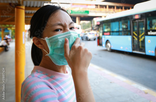 Tired asian child girl cough wearing hygienic mask,stressed worried about air pollution problems,toxic fumes,PM 2 Wallpaper Mural
