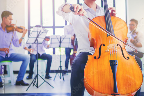 A musician man is practicing the cello playing with the melodiousness. Selected focus. - 318817872