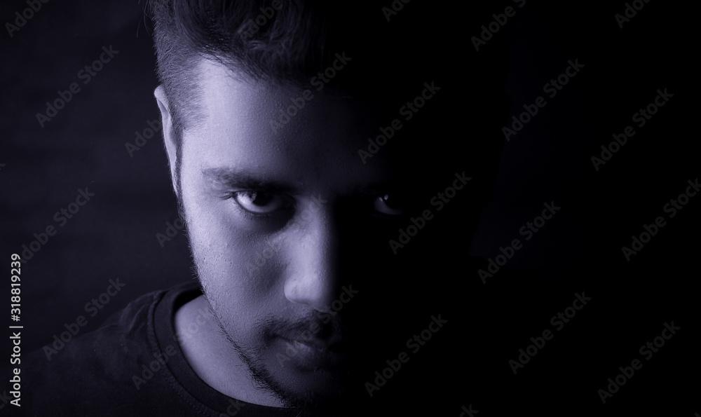 Fototapeta Portrait Of Serious Young Man Against Black Background