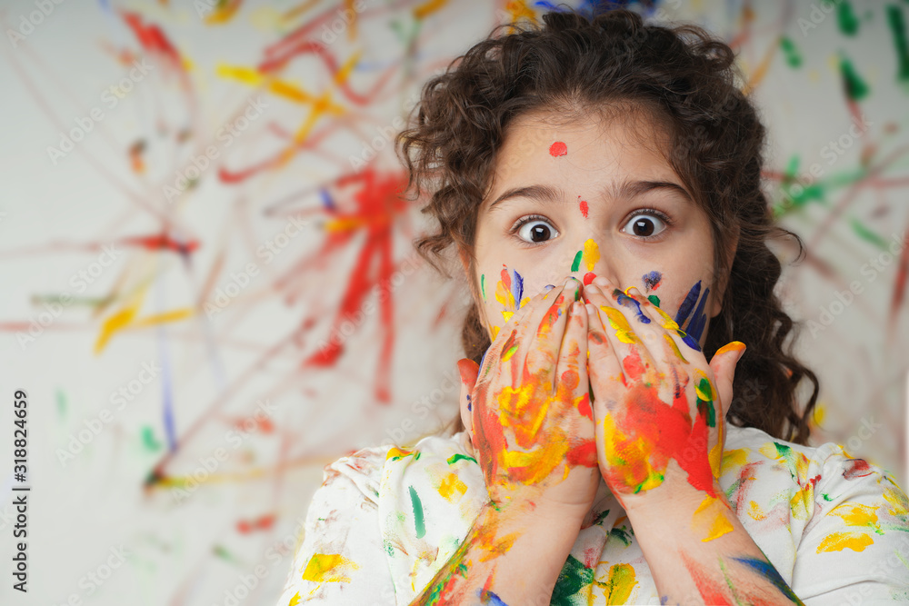 Fototapeta portrait of smiling little girl looking through her colorful hands and cheek  painted in kids room .  fear