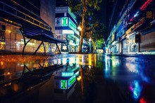 Reflection Of Illuminated Buildings In Puddle At Night