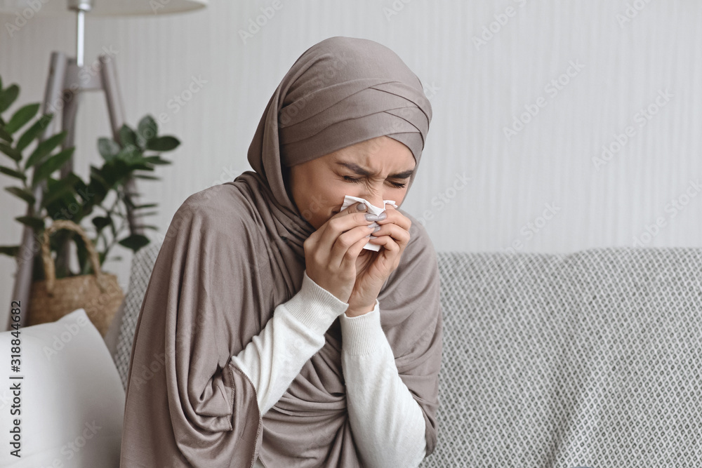 Fototapeta Sick muslim woman blowing runny nose to napkin at home