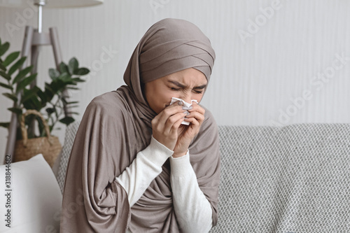 Fototapeta Sick muslim woman blowing runny nose to napkin at home