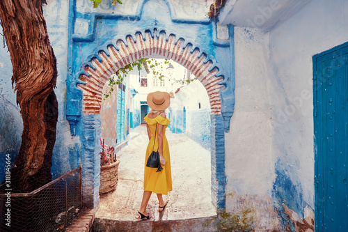 Obraz Colorful traveling by Morocco. Young woman in yellow dress walking in  medina of  blue city Chefchaouen. - fototapety do salonu