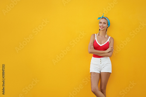 Obraz Summer urban fashion. Fun and colorful. Young pretty happy woman in shorts posing against yellow wall. - fototapety do salonu