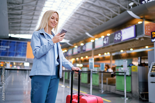 Fototapeta Travel and technology. Online check-in. Female traveler using smartphone waiting for boarding near registration desk line. obraz