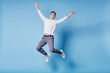 Colorful studio portrait of happy young man jumping against blue background.