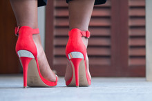 Low Section Of Woman In Red High Heels Standing On Floor