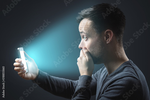 Appalled man looking at his glowing smartphone screen Canvas Print