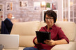 Old elderly woman sitting on the sofa and using a digital tablet PC in cozy living room