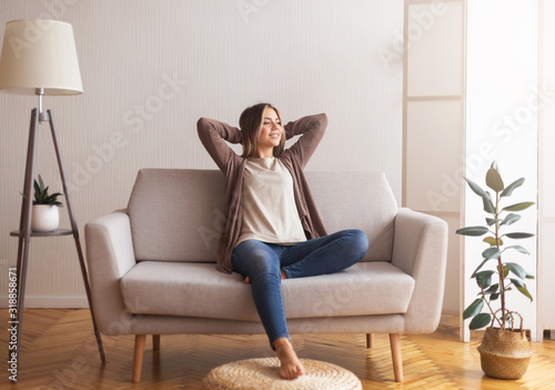 Stampa su Tela Millennial girl relaxing at home on couch