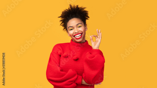 Happy black girl gesturing ok sign and smiling