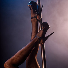 cropped view of stripper in fishnet tights and heels near pole on blue with smoke