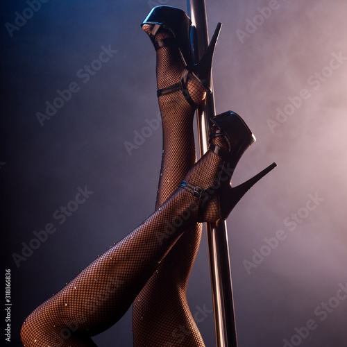cropped view of stripper in fishnet tights and heels near pole on blue with smoke - fototapety na wymiar