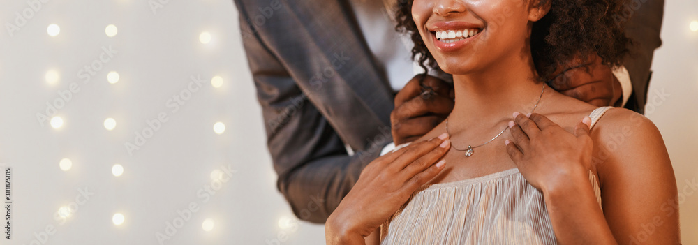 Fototapeta Cropped of man putting beautiful necklace on woman neck