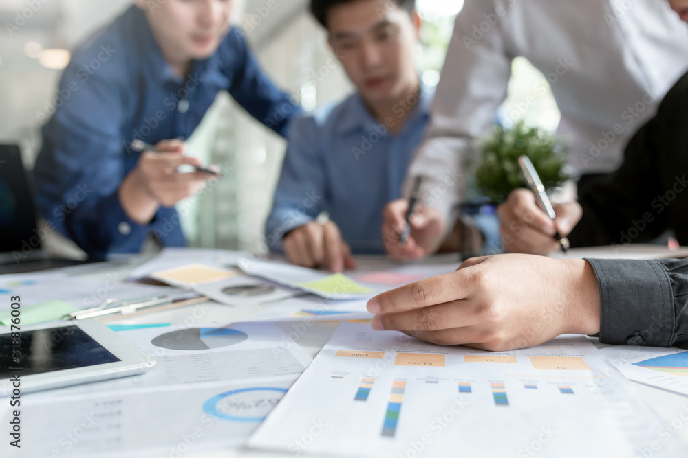 Fototapeta New generation group of asia businessman in smart casual wear together to analyze the financial data graph at work.